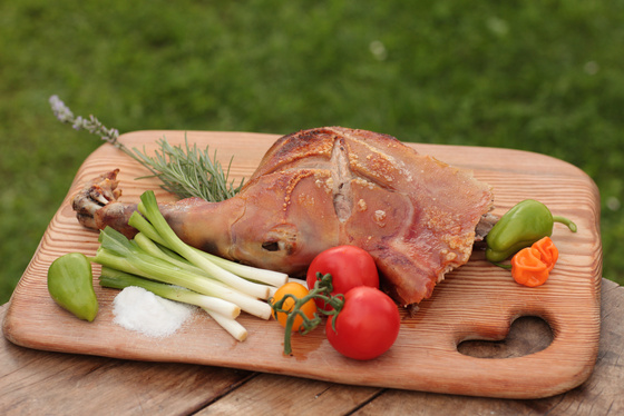 Roasted pork leg served with vegetables on a wooden board.