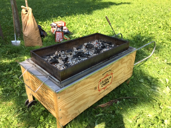 La Caja China roasting box on a summer day located on a nice lawn.